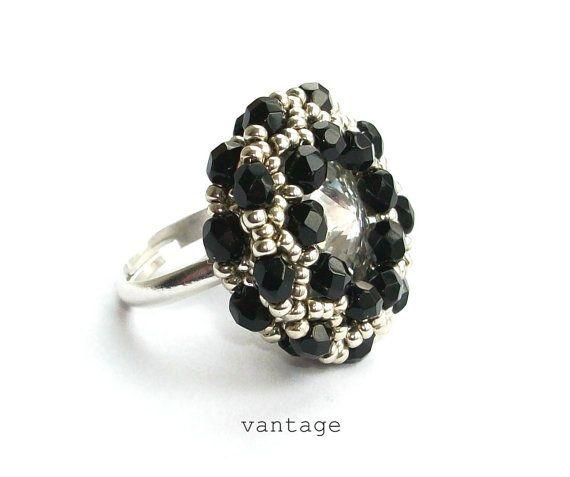 Istruzione in rilievo anello con Swarovski Crystal  Un cuscino di Rocailles argento con 3 strati di cristalli neri circondano una pietra di cristallo scintillante di Swarovski. Il gingillo perfetto.  ~ Il diametro dellanello è di circa 1 o 25mm, 10 mm di altezza  ~ Lanello ha una fascia regolabile nella piastra di argento di qualità migliore, taglia unica.  ======================&#x3D...
