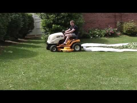 Riding lawn mower rear attachment device videos of Tarp Tow showing the device moving wet and old leaves, moving pine needles, moving storm damaged tree limbs and fallen tree trunks, and moving bush trimmings using a tarp or plastic sheet with ease.