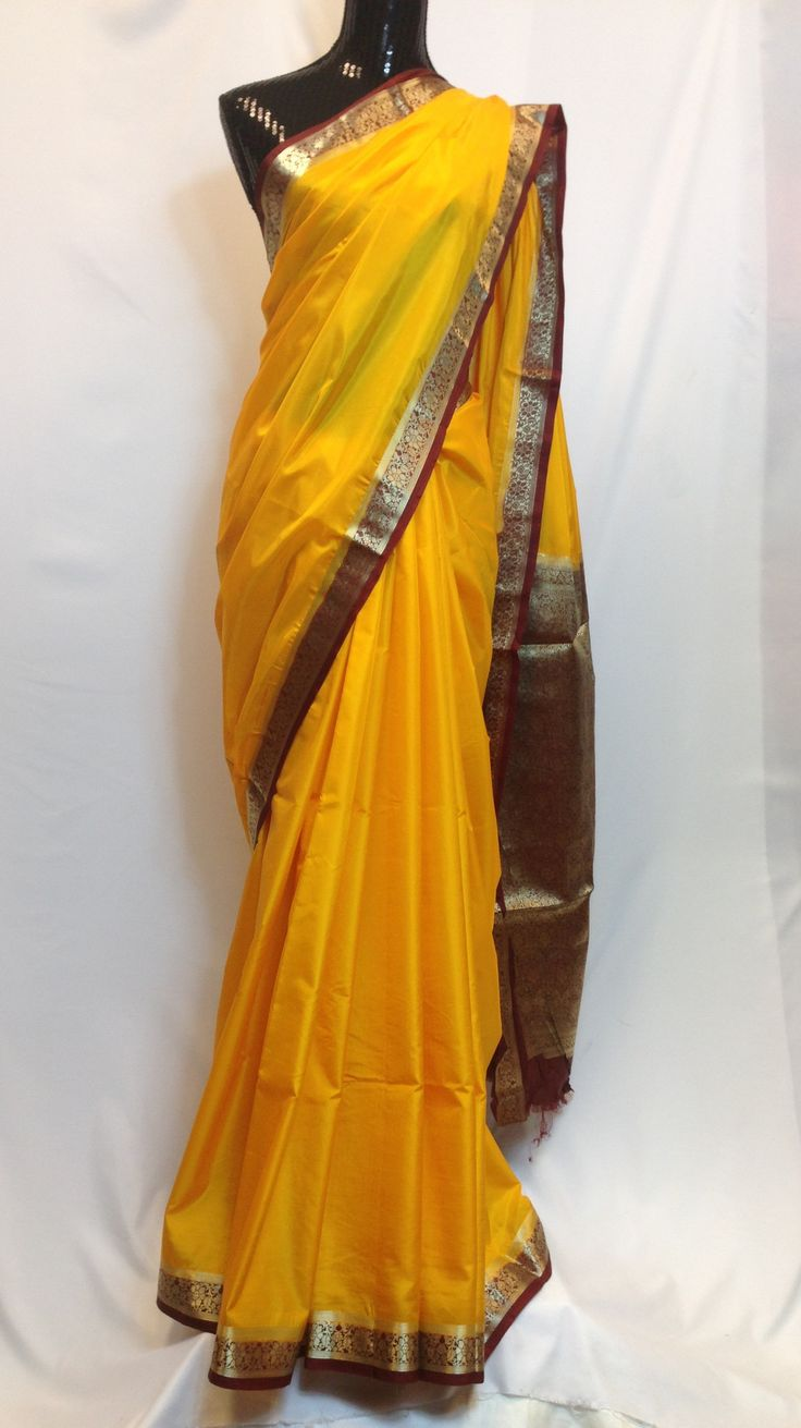 Stylish and gorgeous yellow silk saree with maroon golden silk zari border and heavy silk zari woven pallu makes this indian apparel to die for. High in demand due to its crepe like texture.Gives you