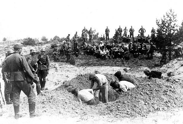 Jews digging pits, apparently in the Kužiai forest not far from Siauliai. The Einsatzgruppen would later use these pits to bury the Jews of Siauliai after they were murdered. The photograph was taken by a member of the SS.