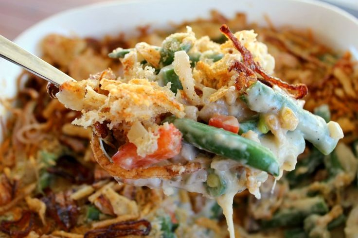 A traditional side dish becomes a gourmet green bean casserole with the addition of red bell peppers and grated Parmesan cheese.
