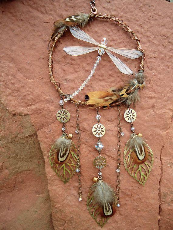 Esta mano-hecho a mano maravillosamente libélula-atrapasueños cuenta nuestra libélula hecha a mano colección de sol, Crystals de Swarovski, flores de bronce, campanas y hojas, intrincado mano-atado con alambre junto en aro martillado conectado un surtido de latón y alambre de bronce.  Hojas y las campanas hacen un sonido suave de la marca. Colgar en el interior en una ventana ventosa o al aire libre en un patio cubierto. Colgar al sol para prismas de la luz del deslumbramiento.  Un…