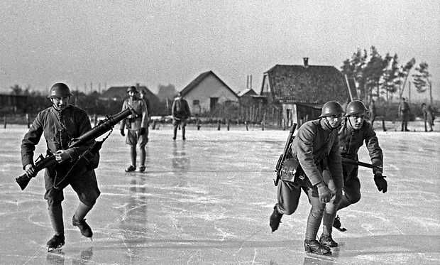 ERGENS IN NEDERLAND - Met wapen en op de schaats oefenen gemobiliseerde militairen in de winter van 1940 in het bevroren inundatiegebied van de Hollandse Waterlinie. (Inundatie = het onder water zetten van lage gronden, als middel tot verdediging). De linker soldaat met een luchtgekoelde mitrailleur in zijn hand. ANP PHOTO CO ZEYLEMAKER