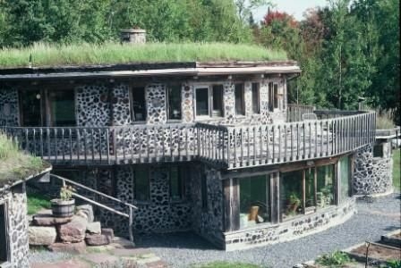 Round cord wood two story with decks built into hillside for Cordwood home plans