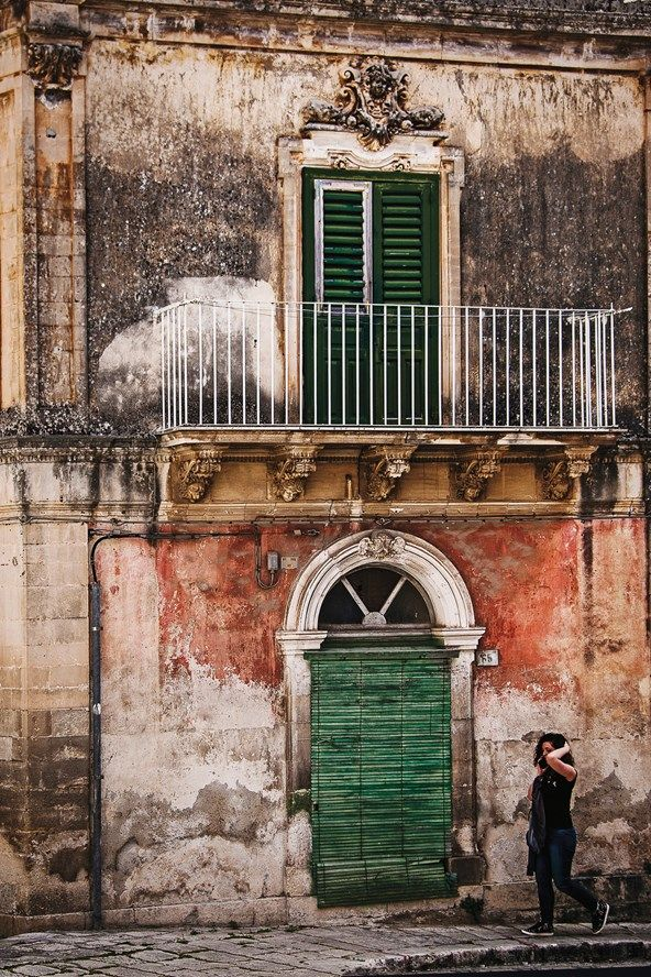 Classic Sicilian faded grandeur - an age-worn old house in Ragusa, Sicily, with distressed walls and carved decoration over the arched door and window