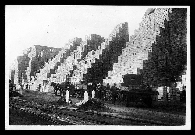 WW1: Boxes of food supplies being piled up. The number of boxes is so vast that the men working there are dwarfed by the sheer size of the stores. Boxes are being unloaded from two horse-drawn carts and a truck. In the foreground there are tracks, possibly for a light railway.    With around two million men in the British Army alone, it was a huge undertaking to feed them all by National Library of Scotland, via Flickr