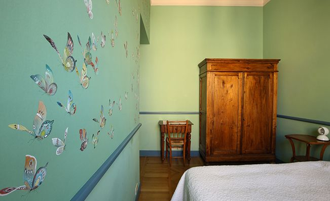 Bedroom wall in Misha's modern chinoiserie, Butterflies wallpaper design on Green E merald dyed silk.