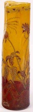 Emile GALLE (1846-1904), vase cylindrique à col pincé à chaud. Décor de chrysanthèmes, émaillé à chaud sur verre rouge et jaune nuancé avec des rehauts d'or. Signé sous la base à la roue : « Cristallerie de GALLE à Nancy » « Modèles et décor déposés » Hauteur : 31,5 cm. Diamètre de la base : 8,5 cm.