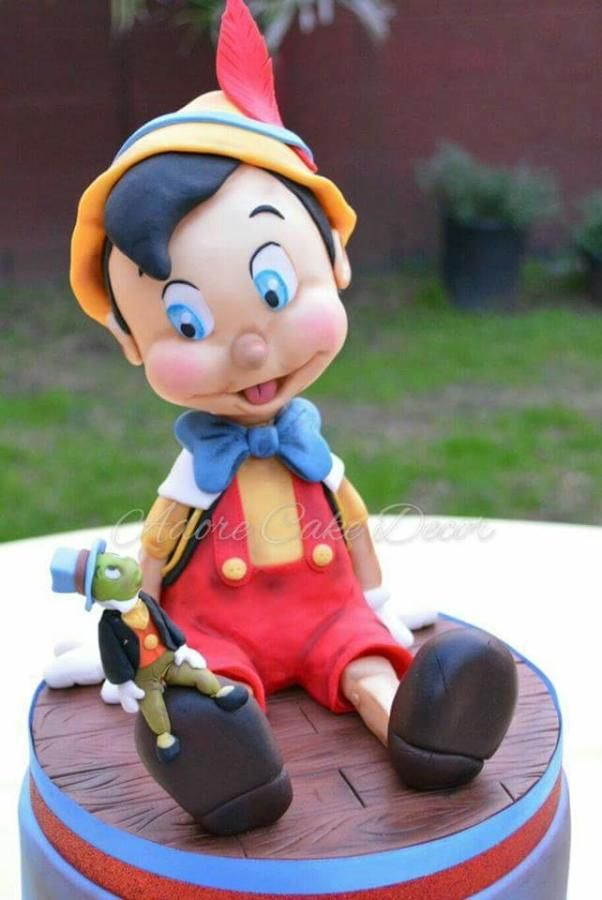 This is an 8 inch cake with Pinocchio sitting on top. I made this cake for my own baby shower to celebrate the arrival of our 4th boy! Pinocchio is made out of RKT, modeling chocolate, and fondant.