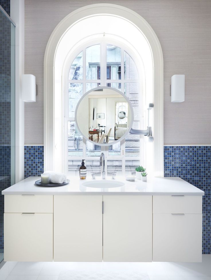 The master bath—anchored by an enormous arched window above a bespoke vanity—carries on the serene feel of the bedroom with its custom indigo Studium tiles and simple sconces from John Salibello.