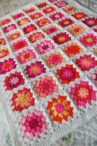 Manta de grannies, con fondo blanco y tonalidades de rojo, al amarillo, pasando por naranja, rosa, fucsia, magenta...