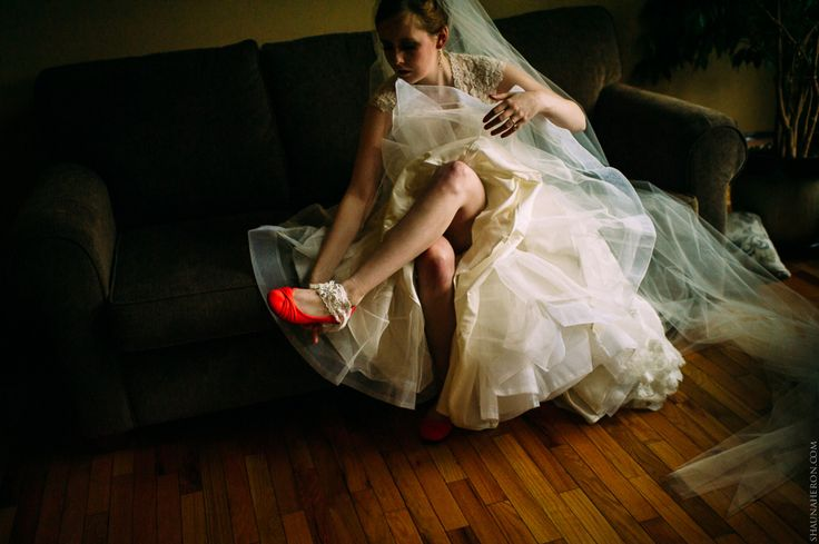 bride in white lace dress with red shoes removes garter