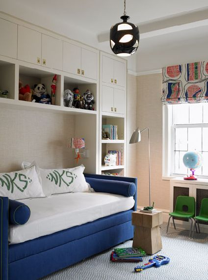 Katie Ridder    Chic boy's room with white built-ins cabinets shelves, royal blue velvet daybed, white & green monogrammed bedding and pillows, green chairs, chrome floor lamp, white blue green red roman shade, modern light pendant and blue rug.