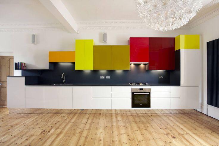 Cucina moderna con le ante dei pensili in vari colori: arancio, giallo, senape e rosso per creare un look moderno e divertente