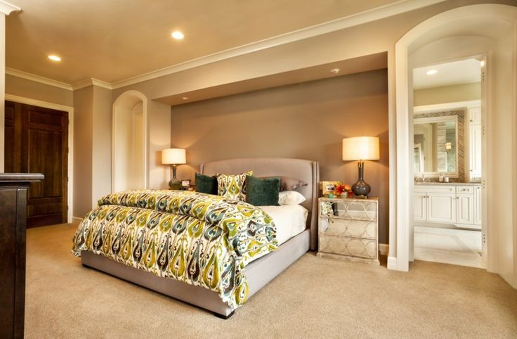 The use of simple taupes and tans lets the use of color and furniture pieces stand out. The dark wood of the furniture give weight to the room while the mirrored bedside tables add interest. The brightly patterned bedspread and pillows commands attention, making the bed the focal point of the room.