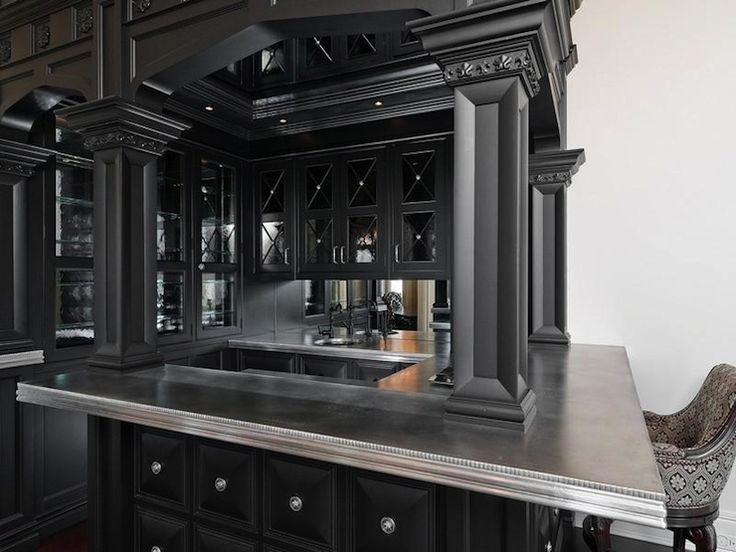 Bar with richly detailed black cabinets &  columns, and zinc countertops...