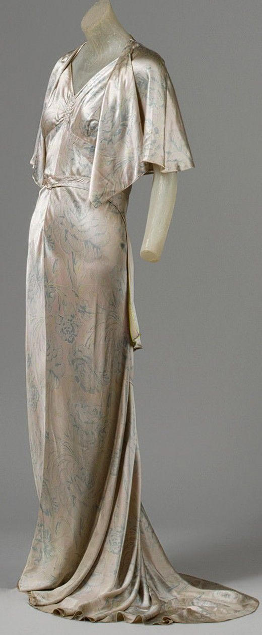 """The elegant evening gown above is typical of 1930s fashion. Silk was a popular fabric that largely come into vogue when Jean Harlow, made her appearance in movies, mostly playing the part of a glamorous, spoiled woman. The """"train"""" finally came back into style after being out of fashion for thirty years."""