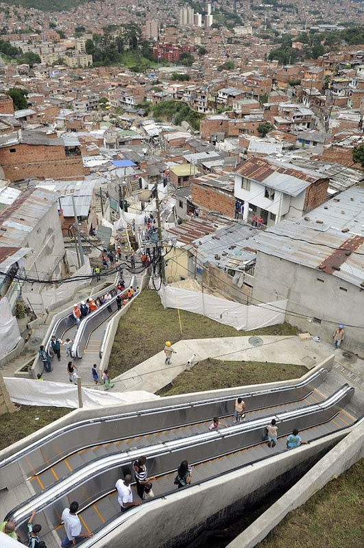 Colombian shanty town installs giant outdoor escalators to relief of residents spared a trudge up steps (equivalent to climbing 28-storey building)    The escalator is 384 metres (1,260ft) long but is divided into six sections so people living on all parts of the hillside have easy access to it.  A giant outdoor escalator will cut their journey from 35-minutes to just six.
