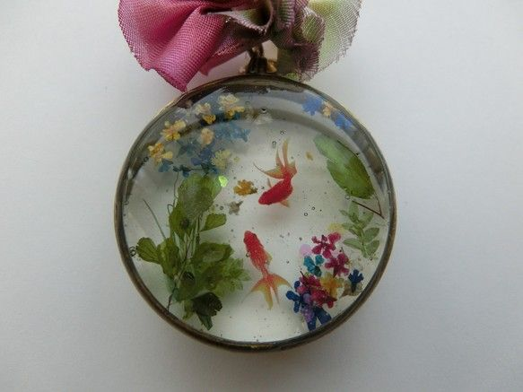 Beautiful example of resin jewelry. Miniature fish and flowers embedded into ice resin inside a bronze pipe ring pendant tray with an open back for transparency. Ribbon necklace by 密会金魚 バックチャーム(お花入り)