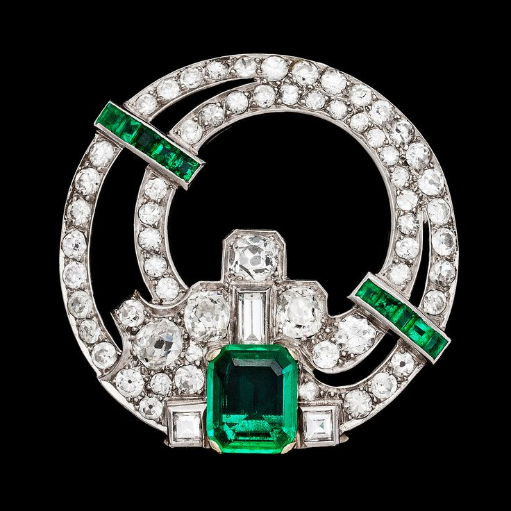 An Art Deco Columbian emerald and diamond clip, 2 cts, resp. 4 cts. 1930's.  platinum. L. 3,5 cm.