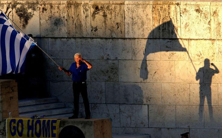 Een demonstrant zwaait met de Griekse vlag tijdens een protest voor het parlement, in Athene, Griekenland.