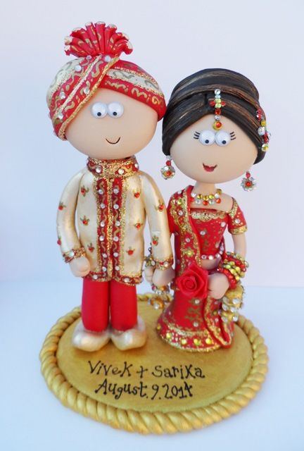 Indian Bride & Groom wedding cake topper. Handmade & totally personalised to look like the couple. Any outfits/poses are possible, something like this would be £149.99 for the couple, £9.99 for a base (they don't need on to stand up). NOT EDIBLE, I send my work anywhere in the World. www.indian-wedding-cake-toppers.com for my Indian/Pakistani work.