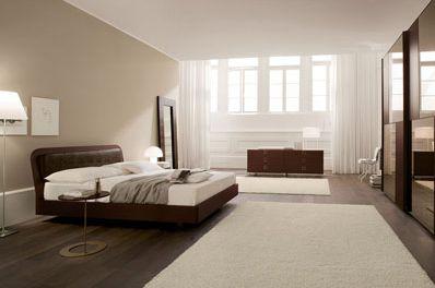 Il letto marrone su una parete color tortora