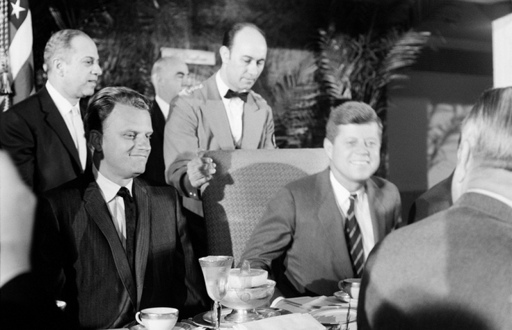 Billy Graham has met with and ministered to a dozen presidents, from Harry Truman to Barack Obama. Here he joins newly inaugurated president John F. Kennedy at a national prayer breakfast at Washington's Mayflower Hotel in February 1961.