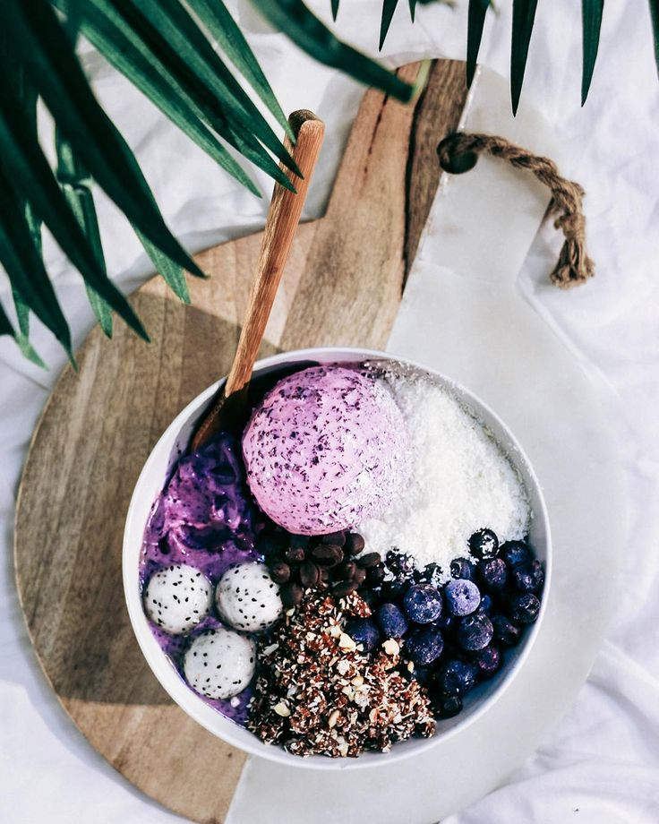 """""""With a scoop of homemade blueberry choc ice cream; the base was blended blueberries, fro nanas and acai powder. I finished it off with coconut shreds, fro blueberries, cashew based rawnola, dragon fruit balls, and carob chips. So delicious!"""""""