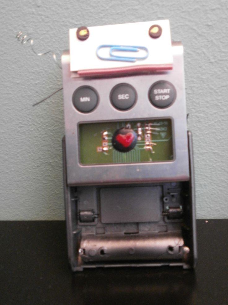 Kookwekker met kapotte draadjes, niet te repareren maar wel leuk om er een robot van te maken met een nagellak hartje en een paperclip als mond. De delen zijn in elkaar geklemd, de kop erop geplakt met dubbelzijdige tape.