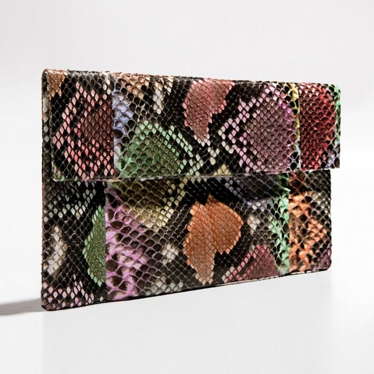 Black multi coloured python clutch by Verinosa Add a dash of creativity to your outfit with this cheerful multi coloured clutch. An eclectic melting pot of inspiring handmade artful patterns applied on authentic python. The perfect clutch for a unique fabulous eye catching look.Designer Colour: Black Multi ColouredGenuine Python snakeskin: IndonesiaInterior: Suede lining and debossed designer letteringMagnetic-fastening front flapAvailable with and without removable chain strapDimensions…