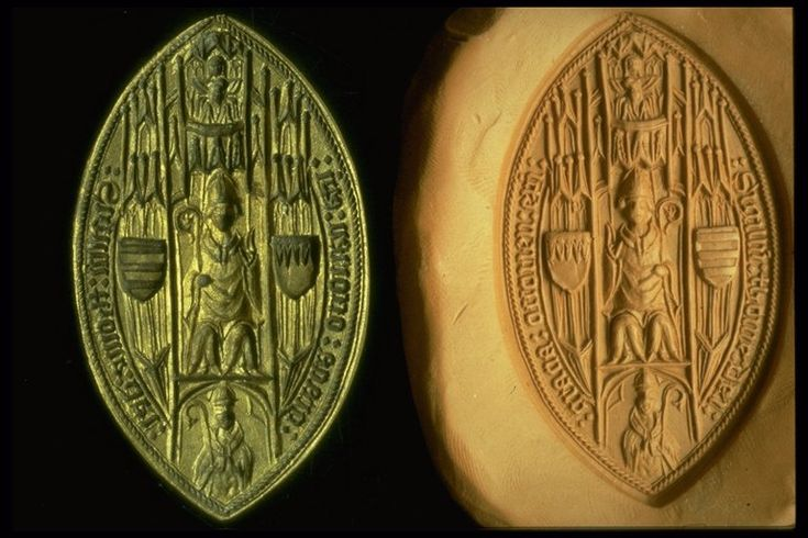Seal matrix This vesica-shaped (pointed oval) seal matrix belonged to Bishop Thomas Barry. It is engraved with the design of a seated bishop under a canopy with the Trinity above and a praying bishop below. The seated bishop is flanked by two shields of arms (chief indented and barry of seven). Around the edge is an inscription in black letter: ':sigillu:thome:dei:/:gracia:ossorien:epi'.  Production Date: Late Medieval; early 15th century