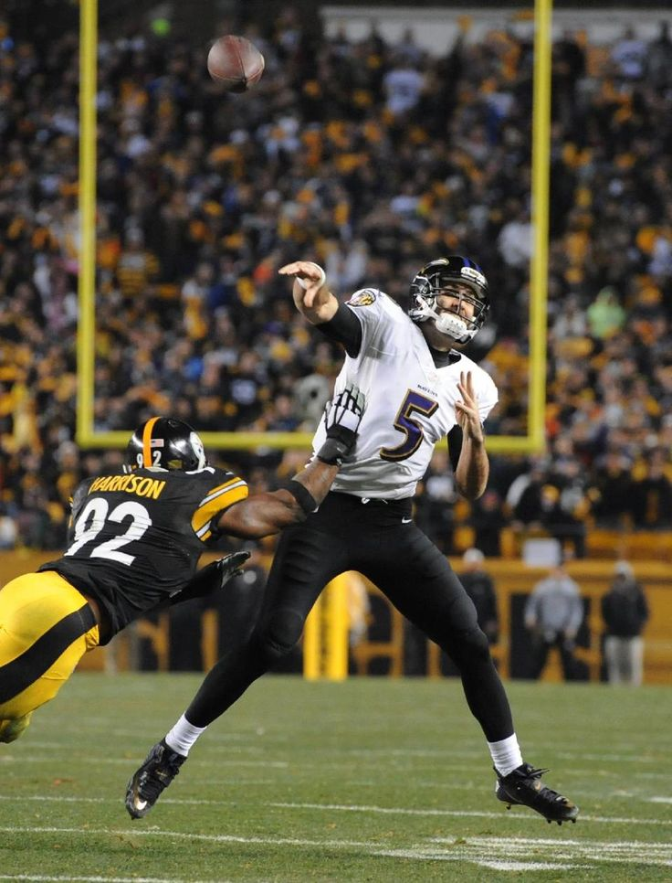 Baltimore Ravens quarterback Joe Flacco looks to pass as he scrambles away from Pittsburgh Steelers outside linebacker James Harrison (92) in the second quarter of an NFL wildcard playoff football game, Saturday, Jan. 3, 2015, in Pittsburgh. (AP Photo/Don Wright)