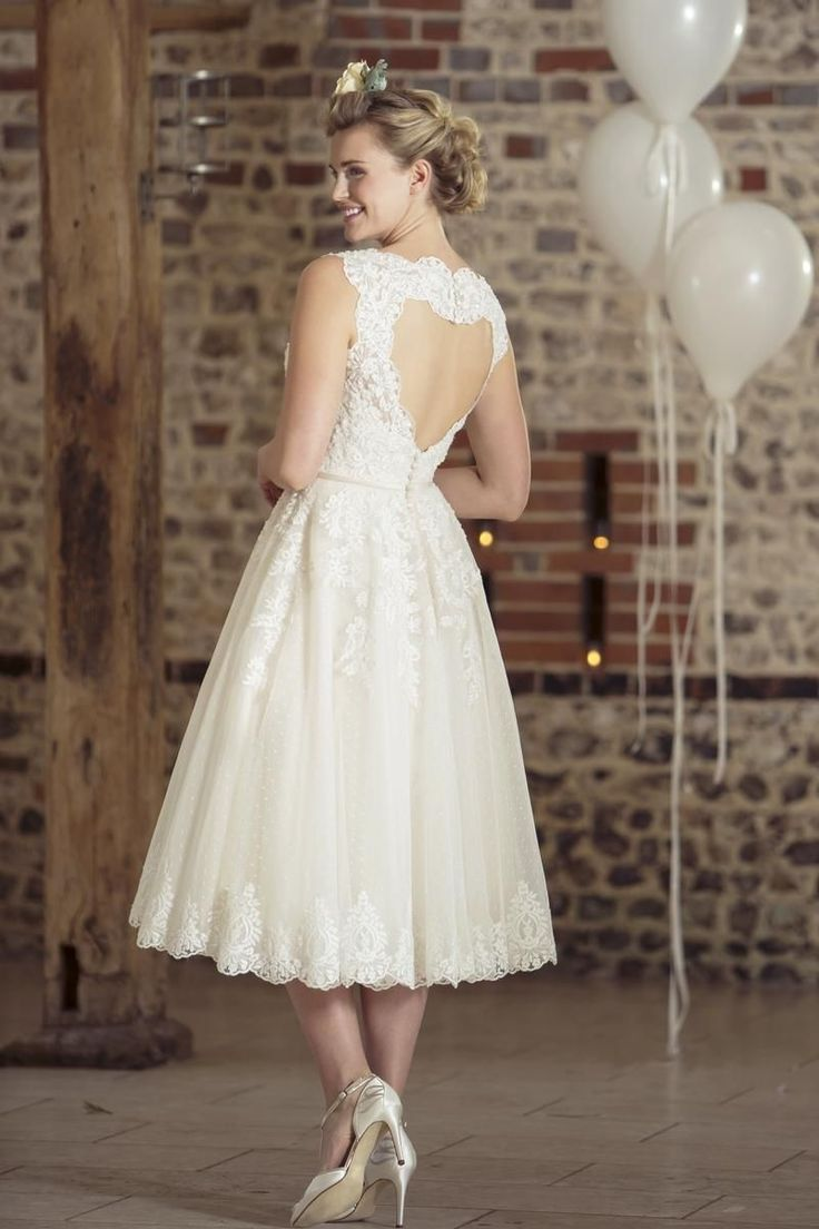 W236 - This short and sassy tea length bridal gown features a pretty beaded lace appliqued onto a 1950's inspired polka dot tulle. This stylish frock has a statement keyhole 'heart' back with a zip closure and button trim.