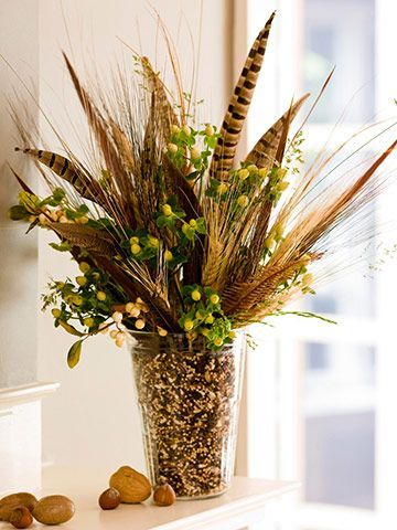 Eclectic by Nature: The natural look often is best left untamed and offbeat. This bouquet mixes faux greenery, ornamental grasses, and pheasant feathers with birdseed as filler. Editor's Tip: Rather than filling the entire vase with birdseed, arrange the tall elements in a smaller vase and set inside a larger vase. Then fill the space between the two vases with birdseed.