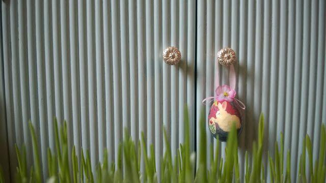 Valkokullanvärinen kukkanuppi jäänsinisessa yöpöydässä.