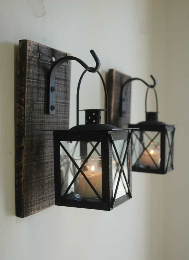 Lantern Pair with wrought iron hooks on recycled wood board for unique wall decor.