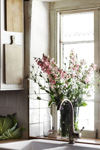 bouquet by the sink, boards hanging off the cupboard side