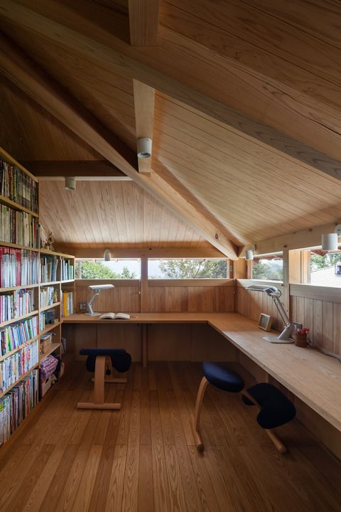 Office with slanted roof, bookshelves and long desk; light wood interior.