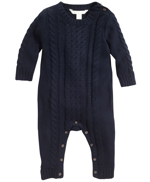 Babydress flettestrikket Fin babydress med knappelukking på skulder og nedentil. Fint flettestrikket mønster. 100% bomull i myk og god kvalitet. Vask 40ºC
