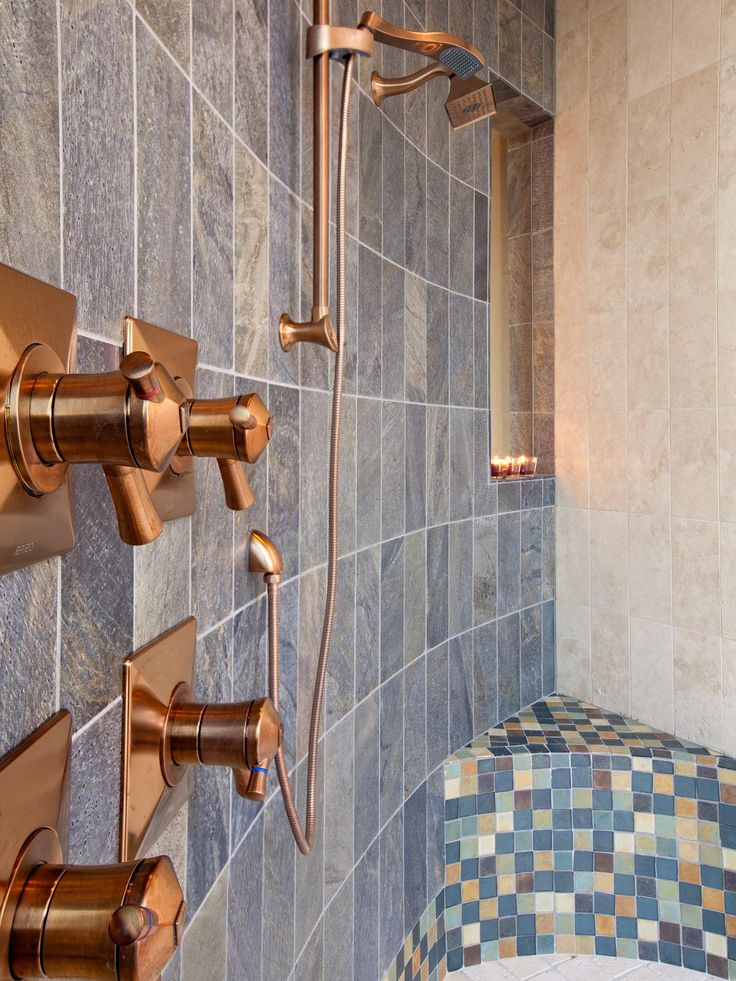This customized walk-in shower features brushed bronze fixtures and a tile bench.