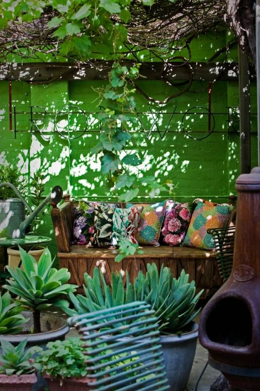 A summer oasis...dappled light...brightly patterned cushions & lush plants..what else could you need?