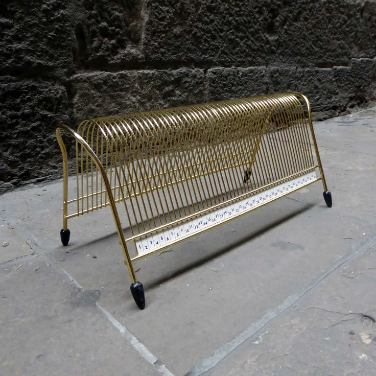 This Mid Century Modern brass wire record rack is organizational and display perfect! Mid Century Modern original wire record rack made in gold brass and raised on 4 little legs. It has capacity for 50 vinyls. Ideal for collectors and music lovers.  It's very decorative and it'll also look perfect for magazines, mail, paperwork, files, etc. In …