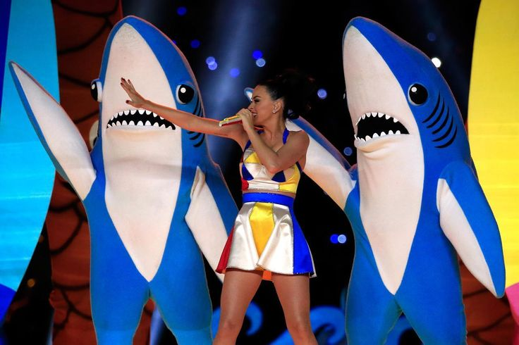 """Katy Perry is Making Left Shark Onesies Happen Because DIY-ing a Left Shark costume is so last month, Katy Perry is now selling replicas of the Super Bowl celebrity's outfit. On Monday, the """"Fireworks"""" singer tweeted that a onesie version resembling the large dancing fish could be bought online through her own ecommerce shop. The light blue one-piece suit features a shark's face on the front, a hood, and KATY PERRY in big bold letters on the back."""