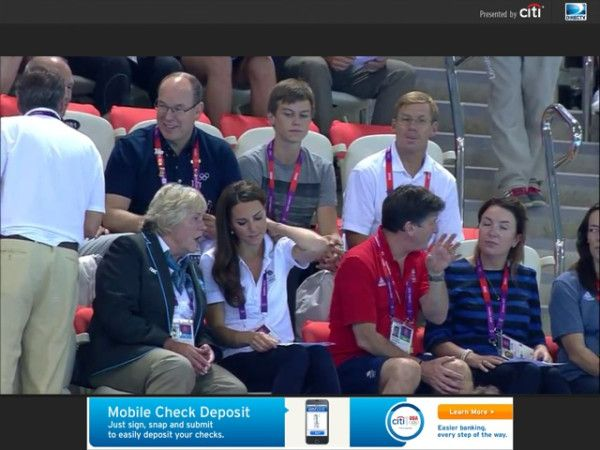 Photo taken at the Olympic Aquatic Center watching women's synchronized swim team. Kate brought back her Stuart Weitzman Corkswoon wedges and Smythe One Button Blazer, as well as her skinny jeans and Team GB polo. You can see Prince Albert of Monaco seated behind Kate in this image.
