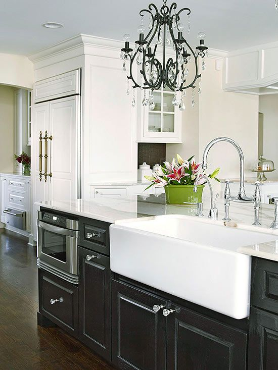 A crisp white farmhouse sink is perfect in a kitchen with high contrast. Sleek black cabinets offset the white farmhouse sink, while black chandeliers above give the room a gothic feel.
