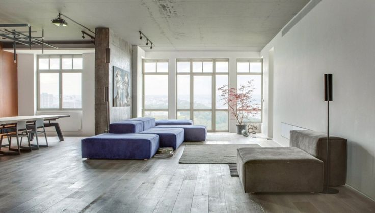 Loft: Cool Urban Loft in Kiev, Ukraine Designed by 2B Group, Stunning Open Floor Living Room Design from Urban Loft in Kiev by 2B Group showing Brown and Blue Ottomans Seat and Modern Floor Lamp also Red Plants in Pot and Huge Glass Windows