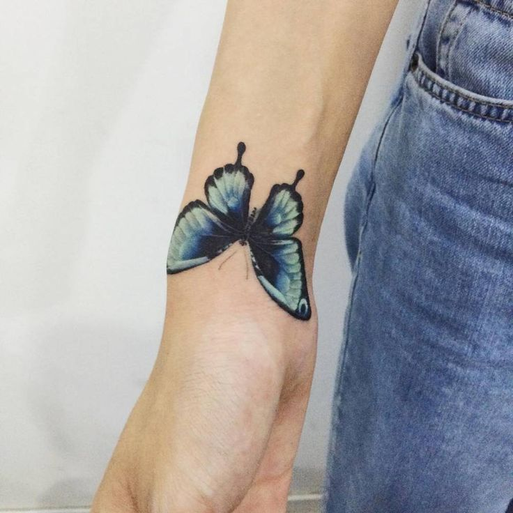 Blue butterfly tattoo on the right wrist. Tattoo artist: Doy