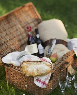 Italian picnic basket filled with home made rustic bread, cheese, olives and wine.