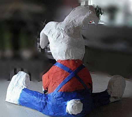 3 Verstevig de nek met een op maat ge-knipte wc rol Knip de wc rol in twee of drie ringen. Maak een inkeping in 2 ringen en schuif die over de knoop in de plasticzak tussen hoofd en romp. Eventueel extra bevestigen met schil-derstape, zodat het hoofd goed is ge-fixeerd. Maak twee dikke lange rollen papier van een opengevouwen krant (of met stroken karton) Dit worden de benen die gespreid zijn  Leg de rollen naast elkaar en zet de romp er   midden tussenin.